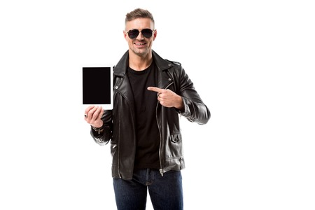 smiling man in leather jacket pointing with finger at digital tablet with blank screen isolated on white
