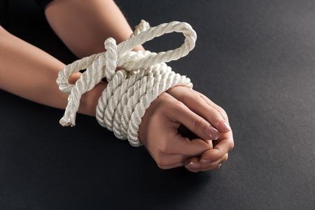 Ausgeschnittene Ansicht weiblicher gefesselter Hände auf schwarzem Hintergrund