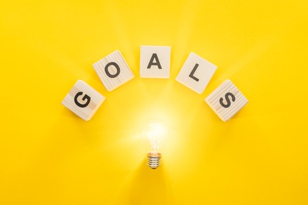 top view of glowing light bulb under goals word made of wooden blocks on yellow background, goal setting concept Imagens