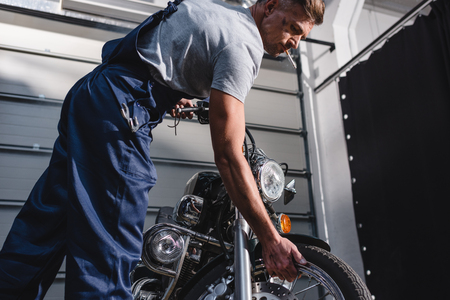 smoking adult mechanic in overalls checking motorcycle tire in garage