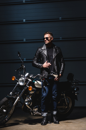 classic guy in sunglasses standing by motorcycle in garage and smoking cigarette
