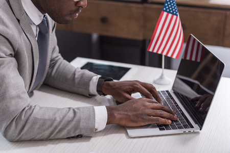 Cropped view of african american businessman typing on laptop keyboard