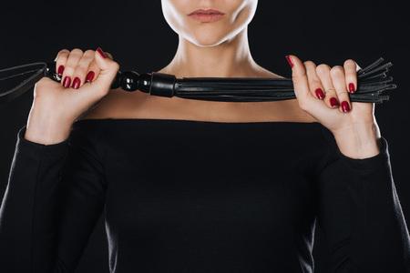 Vue partielle d'une femme stricte tenant un fouet en cuir isolé sur noir