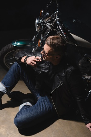 handsome man in black sunglasses and leather jacket sitting on floor next to motorcycle Stock Photo
