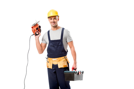 construction worker looking at camera and holding tool box with electric fret saw isolated on white