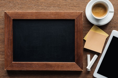 top view of blank chalk board with digital tablet and coffee on wooden background