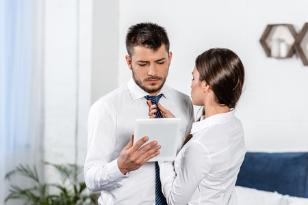 girlfriend tying boyfriend tie while he using tablet in morning at home, social role concept Stock Photo