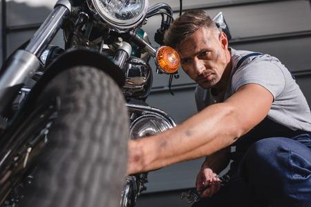 handsome adult mechanic fixing motorcycle tire in garage Reklamní fotografie