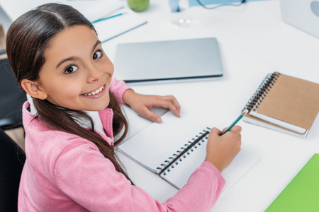 adorable schoolgirl looking at camera and writing in notebook during lesson