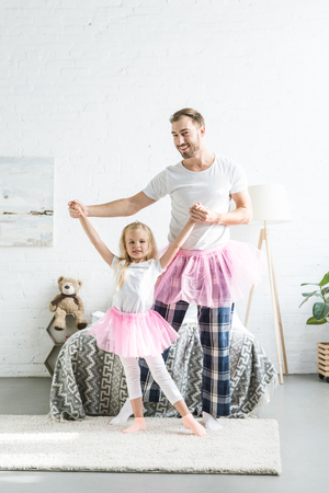 happy father and daughter in pink tutu skirts holding hands and dancing together at home Foto de archivo - 112991317