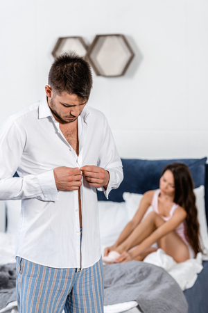boyfriend buttoning shirt and preparing for work in morning at weekday, girlfriend wearing socks on bed, gender stereotypes concept Stock Photo