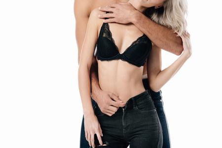 Ausgeschnittene Ansicht eines Mannes, der die Jeans einer Frau isoliert auf Weiß öffnet Standard-Bild