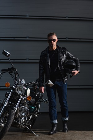 stylish biker in black sunglasses and leather jacket standing by motorbike and holding helmet