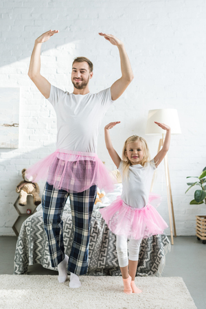 happy father and adorable little daughter in pink tutu skirts dancing and smiling at camera Foto de archivo - 112991381
