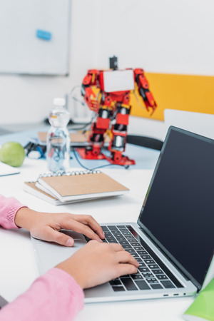 cropped view of schoolgirl sitting at table with robot model and using laptop with blank screen during STEM lesson Stok Fotoğraf