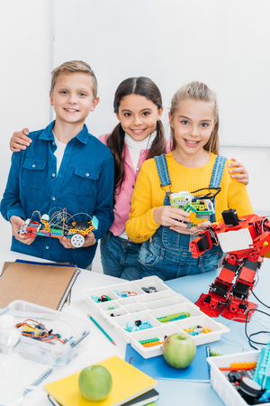 smiling schoolchildren looking at camera and holding handmade robots in classroom