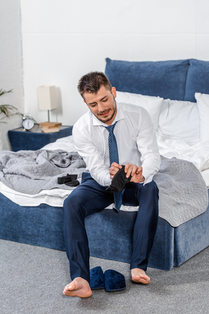 handsome man sitting on bed and wearing socks in morning in bedroom