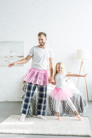 happy father and adorable little daughter in pink tutu skirts holding hands and dancing together at home