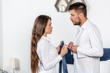 handsome boyfriend buttoning shirt, girlfriend holding his tie in weekday morning in bedroom, social role concept Stock Photo