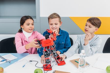 smiling schoolchildren building red electric robot during STEM lesson 写真素材