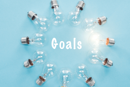 circle of light bulbs with glowing one surronding goals word on blue, goal setting concept Reklamní fotografie