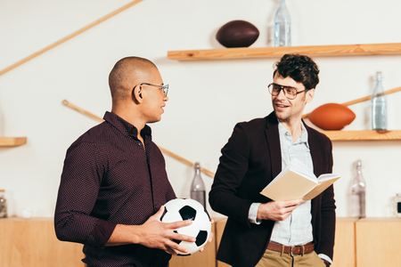 portrait of multiethnic businessmen with soccer ball and book in cafe