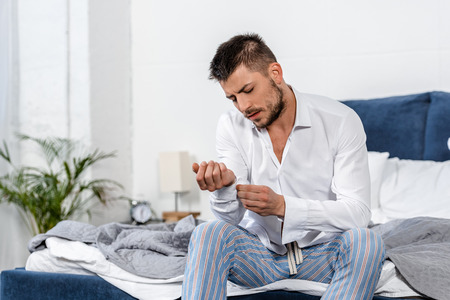 handsome man sitting on bed and buttoning cuff in weekday morning in bedroom