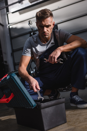 mechanic sitting by toolbox on floor in garage Banque d'images - 112989054