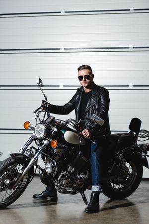 handsome man in sunglasses sitting on motorcycle and looking at camera