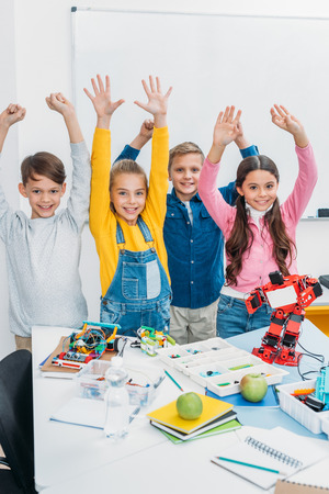 happy schoolchildren with raising hands standing at desk with plastic robots and details in stem class