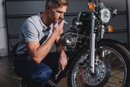 handsome adult mechanic smoking and holding wrench while fixing motorcycle in garage