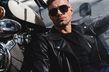 handsome classic guy in sunglasses sitting by motorcycle in garage Stock Photo