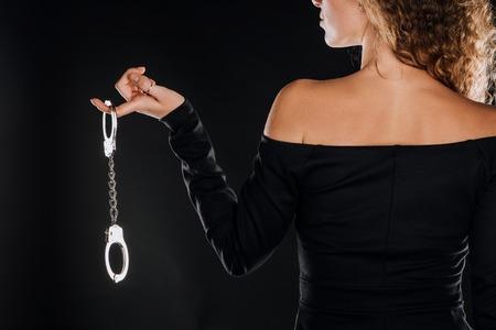 Vue arrière d'une femme bouclée tenant des menottes en argent isolées sur fond noir