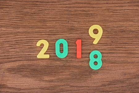 top view of date made with colorful numbers symbolizing change from 2018 to 2019 on wooden background Stock Photo