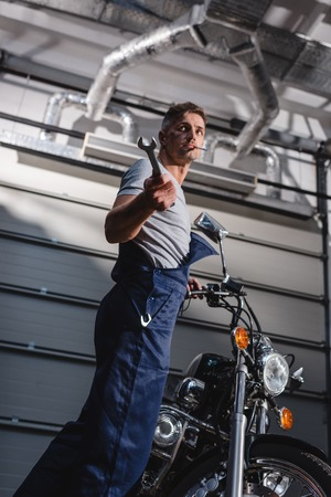 mechanic with wrench in hand next to motorbike in garage