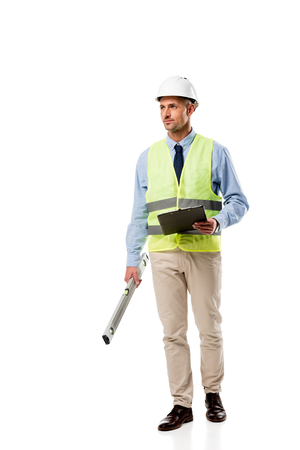 handsome engineer holding spirit level, clipboard and looking away isolated on white Stock Photo - 112990993