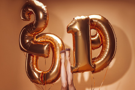 cropped image of woman lying under balloons with 2019 numbers at party on beige, new year concept Stock Photo