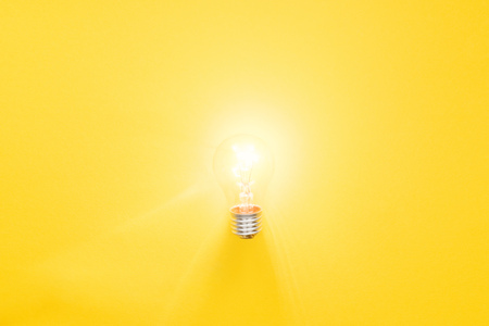 glowing light bulb on yellow background, having new ideas concept