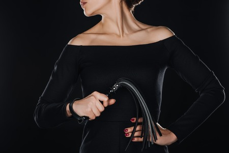 partial view of woman with hand on waist holding leather flogging whip isolated on black
