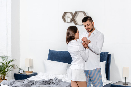 handsome husband buttoning cuff and wife buttoning his shirt in weekday morning in bedroom