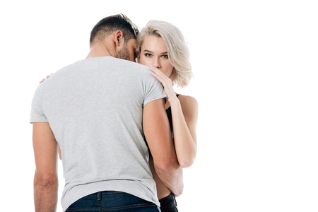 beautiful blonde woman looking at camera and embracing man isolated on white