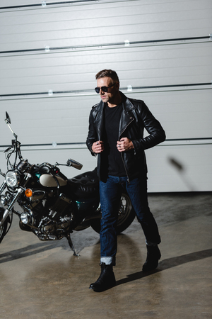 cool guy in sunglasses and leather jacket walking in garage Stock Photo