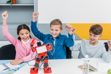 happy schoolchildren raising hands and looking at red handmade robot at desk during STEM lesson