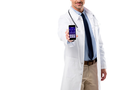 partial view of doctor holding smartphone with health data app on screen isolated on white