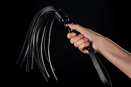 Vue partielle de la main féminine tenant le fouet en cuir isolé sur noir Banque d'images