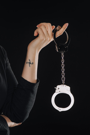 cropped view of woman holding shiny handcuffs isolated on black Stock Photo