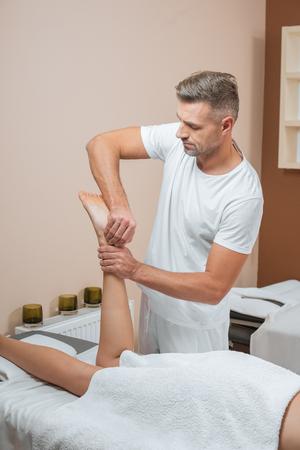 handsome masseur doing relaxing feet massage