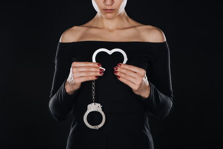 partial view of woman holding opened handcuffs isolated on black Foto de archivo
