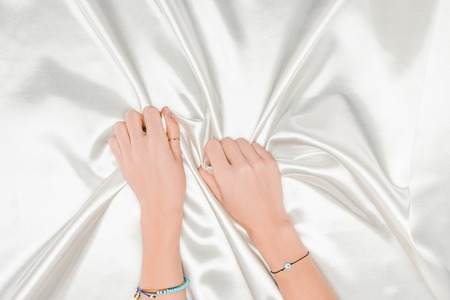 top view of female hands tightly holding shiny white satin cloth