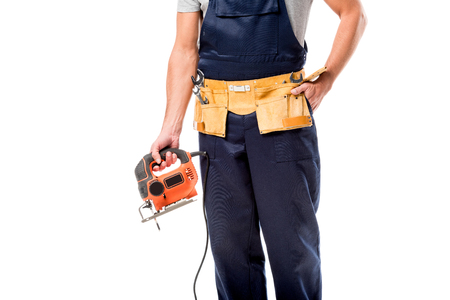 cropped view of carpenter with tool belt holding electric fret saw isolated on white